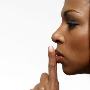 Young Businesswoman with Her Finger on Her Lips --- Image by © Royalty-Free/Corbis