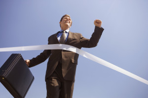 Businessman Crossing the Finish Line --- Image by © Royalty-Free/Corbis