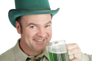 A handsome Irish American man with green beer on St. Patrick's Day.  White background.